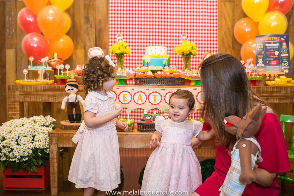 Irmãs e mãe olhando a mesa do bolo