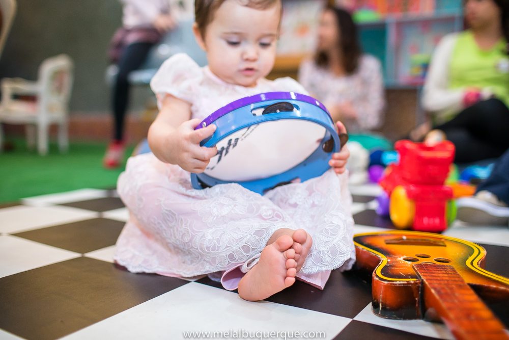Bebê tocando pandeiro de pernas cruzadas