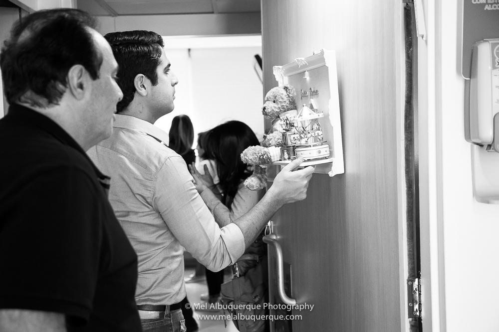 Pai arrumando o quadro da porta da maternidade